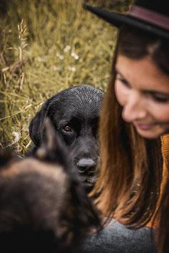 Schwarzer Labrador schaut zwischen Kind und seiner Halterin in die Kamera man sieht nur sein Auge festgehalten von der Hundefotografin Monkeyjolie