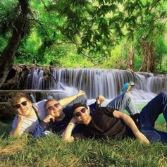 Die drei DJs von Liebenskommando vor einem Wasserfall liegend.