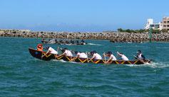 風が強く波が高い中、参加者らは懸命にオールをこぎ、海上からは歓声が上がった=11日、北谷漁港