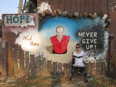 Janis McDavid vor einem Bild mit Nick Vujicic, der ebenfalls ohne Arme und Beine geboren wurde.