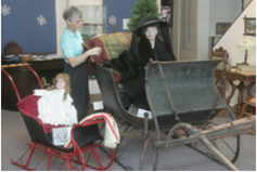 """Suzy Frederick, curator of the Dekker Huis/Zeeland Historical Society Museum, discusses a sleigh, or cutter, on display in the new exhibit """"Winter Memories"""" at the museum, 37 E. Main Ave."""
