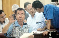 臨時議会の休憩中、議員の質問に答える川満町長=14日午後、議場