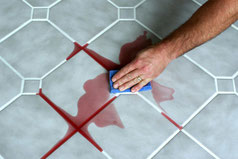 Light gray tile with white grout. A man's hand is using a blue sponge to wipe up a red wine spill.