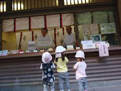 天満宮の二人の宮司さんと、帽子をかぶった三人の子ども