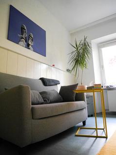 Praxisraum mit Sofa, Bild und Pflanze