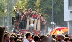 Ein voll besetzter Wagen beim Karneval der Kulturen umringt von Zuschauern. Foto: Helga Karl