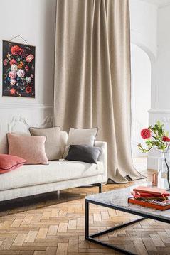 Rideaux beiges mettant en valeur un tableau de roses très Napoléon 3 au dessus d'un canapé moderne