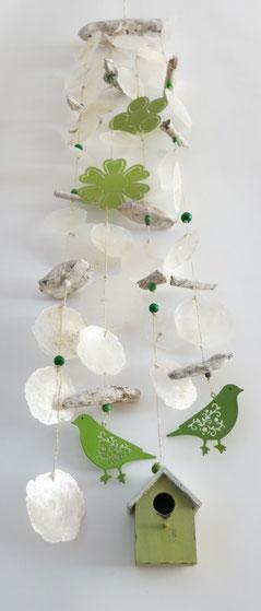 Muschelgehänge mit grünen Vögeln und Holzhaus