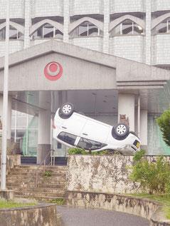 強風で花壇の上に吹き飛ばされた軽自動車=8日午後、県八重山合同庁舎