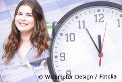 Foto - Junge Frau steht neben einer Uhr und lacht