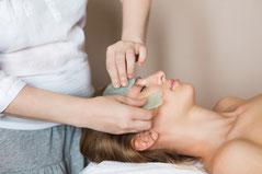 Massage du visage avec deux Guasha en pierre.
