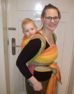 Iris Steger mit Kleinkind im Tragetuch auf dem Rücken