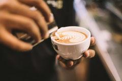 Milchschaum wird in Kaffeetasse gegossen