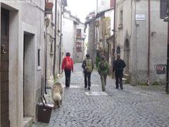 4 personnes de dos marchent dans les rues pavées de ce village des Abruzzes