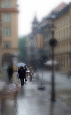 einsame Frau mit Regenschirm in nasser Stadtlandschaft