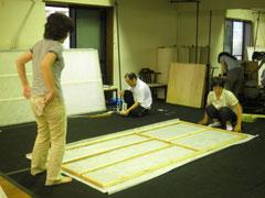 棟梁が組み立てた枠に、シートを貼っていく弟子たち