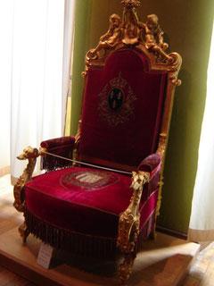 """trône du comte de Chambord. On peut y voir les fleurs de lys, les accotoirs en tête d'hermine, les cartouches ornés du """"H"""" et les armes royales de France sur le dossier"""