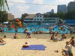 奥には造波プール、手前は砂浜を演出ののんびりできる場所も。 外人のおね~さんたちも日光浴に来てま~す