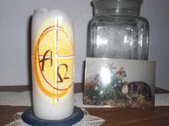Eine Kerze mit Kreuz und Alpha-, Omegazeichen, daneben ein Foto von einer Katze, die auf einem Strohballen neben Tannengrün liegt. Es lehnt an einem großen Einmachglas. Darunter liegen Häkeldeckchen.