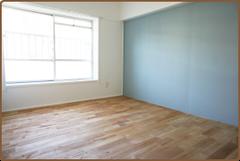 無垢のフローリングに水色のアクセントクロスを貼った居間