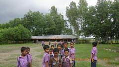 奥に見えるのが学校の校舎。子どもたちの学習環境を守るためにも植林が必要