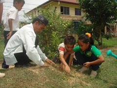 先生と一緒に木を植える子どもたち。