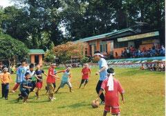 校庭でボールを追いかける子どもたち。校舎の後ろには、「子供の森」計画で育てた森が広がっています