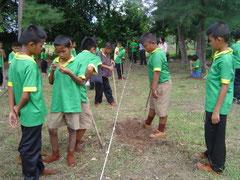 距離を測りながら植林の穴を作っています。