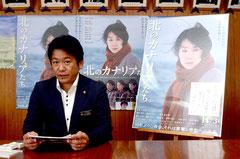 映画のポスターを背に、多数の観賞を呼び掛ける中山義隆市長=石垣市役所