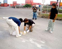 壊れた道路の応急処置を行うすぐやる課の職員(同課提供)