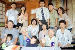 子や孫に囲まれ、新百歳を迎えた呉屋トシさん(前列左から2人目)、加真さん(同4人目)夫妻=17日午前、石垣市新川の自宅
