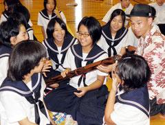 世界最古の管楽器、ディジュリドゥに挑戦する生徒を指導するNATAさん=白保中=