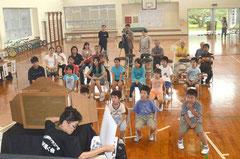 手作りの紙芝居を3人掛かりで操作。児童は食い入るように見つめていた=大本小学校、真栄里。