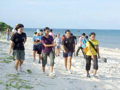 ウミガメ上陸確認調査のため、白保海岸を歩く児童生徒たち=15日夕、白保海岸