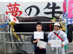 見事牛を当てた(左から)与那覇君と甲斐田さん=26日午後、黒島多目的広場