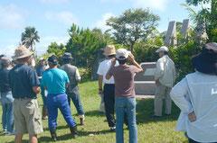 定員を超える35人が参加した戦跡めぐり。青空の下、石堂さんの説明に静かに耳を傾けていた=米軍飛行士慰霊碑前、新川。