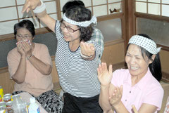 浦添商の得点シーンで、大喜びで踊り出すす関係者。左は感激の表情を見せる母の順子さん=16日午後、石垣市石垣の宮良監督の実家