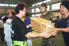 自衛隊員と市民が協力し、救援物資を屋内練習場に搬入する訓練を行った(29日午前)