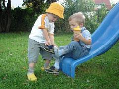 Kinder helfen einander beim Schuheanziehen