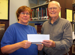 Marla Vizdal, left, President of the McDonough County Genealogical Society, presents a donation to Louis Battin,President of the McDonough County Historical Society, to support the cemetery sign project of the MCHS