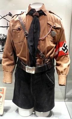 Hitlerjungenuniform aus den 1930er Jahren. Bestehend aus Braunhemd mit Effekten, kurzer Kordhose, Lederkoppel mit Schloss, Schulterriemen, Halstuch und Messer; Ersteller: WerWil, Lizenz:  Creative Com
