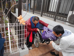 車椅子での参加者を階段から地下へ降ろしている写真