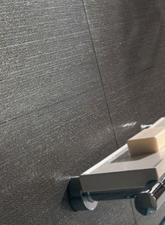 Close up of wall tile with charcoal gray porcelain tile with a linear denim look. There is a wall-mounted chrome and white soap dish with a bar of soap on it.
