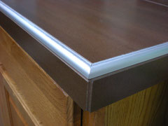 Brushed Nickel Schluter Rondec is used to finish off the edge of a countertop