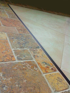 Travertine tile and mosaic border with a Schluter edge metal liner