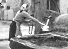 Une femme prenant de l'eau à la fontaine