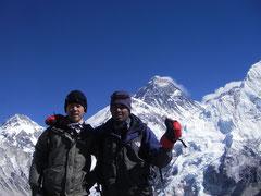 エベレストをバックにガイドと共に(左)