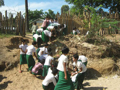 Children cleaning the school grounds