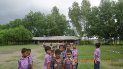 School building is seen behind. Tree-planting is necessary for protecting children's Study environment.