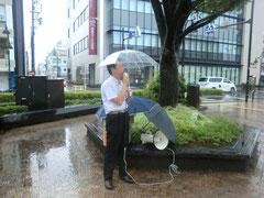 ハンドマイクを雨から傘で保護して実行です